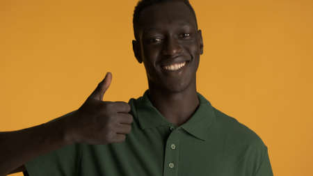 Attractive smiling African American guy looking happy keeping thumb up on camera over colorful background. Like expression