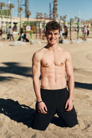 Young attractive sporty guy with torso happily looking in camera resting after workout on hot summer day on beach
