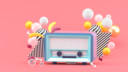 Blue radio amidst colorful balls on a pink background.-3d render.