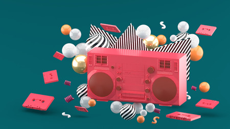 Red radio amidst colorful balls on a green background.-3d render.