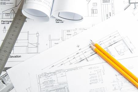 architect: Dibujos de planificación de la construcción en la mesa y dos lápices amarillos