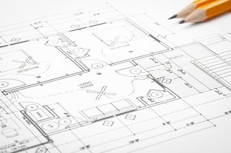 arquitecto: Dibujos de planificación de la construcción en la mesa y dos lápices amarillos