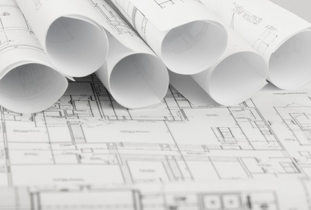 rolls of architecture blueprints and house plans on the table Stock Photo