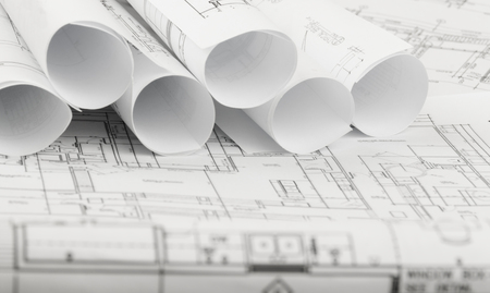 housing project: rolls of architecture blueprints and house plans on the table Stock Photo