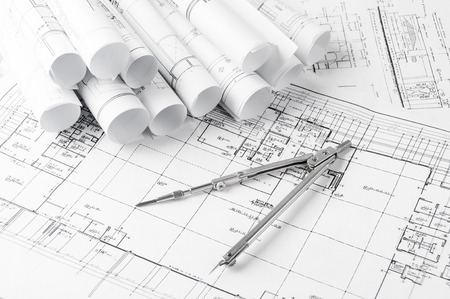 rolls of architecture blueprints and house plans on the table and drawing compass Foto de archivo