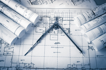 rolls of architecture blueprints and house plans on the table and drawing compass Stock Photo