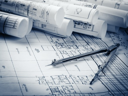 rolls of architecture blueprints and house plans on the table and drawing compass Standard-Bild