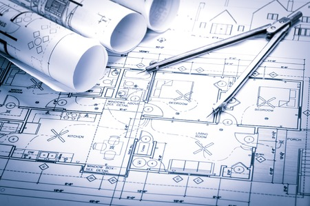 architecture and buildings: rolls of architecture blueprints and house plans on the table and drawing compass Stock Photo