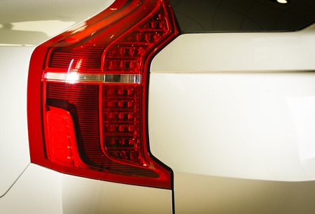 stoplights: Detail of the rear end of a silver car with focus on the brake lights.