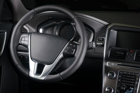 Brand new business car interior in white leather and wood, backseat view