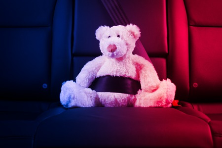 police lights: Teddy bear fastened in the back seat of a car, red and blue police lights