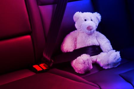 oso negro: Luces de la polic�a Oso de peluche fija en el asiento trasero de un coche, rojo y azul Foto de archivo
