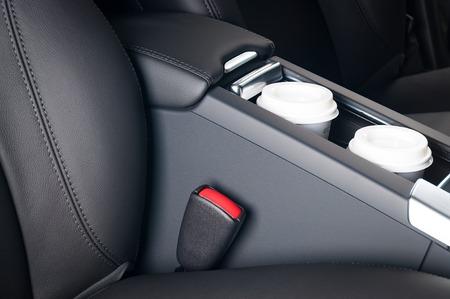 コーヒーを飲みながら運転。車のカップ ホルダーの中の紙のコーヒー カップ。