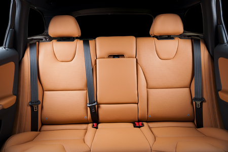 legroom: Back passenger seats in modern luxury car, frontal view, red orange sand leather Stock Photo