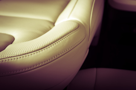 Part of  leather car seat with the unfocused car interior on the background, vintage filter
