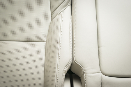 legroom: Back passenger seats in modern luxury car, close-up view, white perforated leather