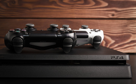 Sankt-Petersburg, Russia - 14 August, 2017: Sony PlayStation 4 Slim 1Tb revision and game controllers on the wood background