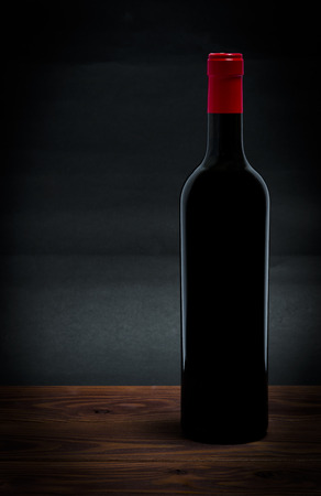 Bottle of red wine on wood table Archivio Fotografico