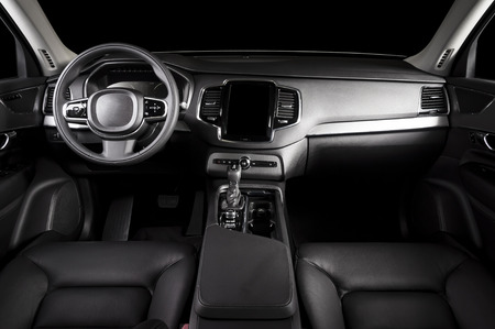 Modern luxury prestige car interior, dashboard, steering wheel. Black leather interior.