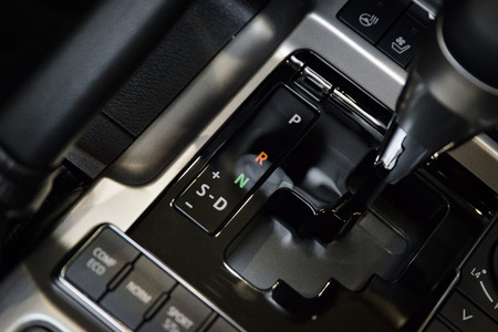 Automatic transmission gear stick of a modern car, car interior details with electronic components