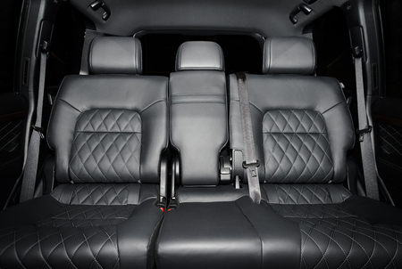 Back passenger seats in modern luxury car, frontal view, black perforated  stitched leather Archivio Fotografico