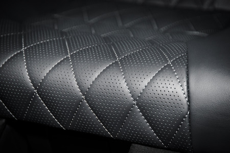 Modern luxury car black perforated leather interior. Part of stitched leather car seat details. Archivio Fotografico