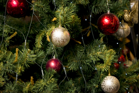 Christmas tree with a balls. Spruce branches with red and golden balls close up. Pine branches with a toys and garland. Greeting card. Archivio Fotografico