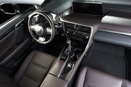 Modern luxury car  interior, dashboard, steering wheel. Red perforated  leather interior