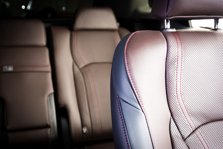 Red leather drivers seat in modern luxury car, blurred back seats in the background, car interior details