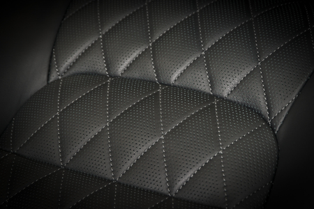 Modern race car black perforated leather interior. Part of stitched leather car seat details.