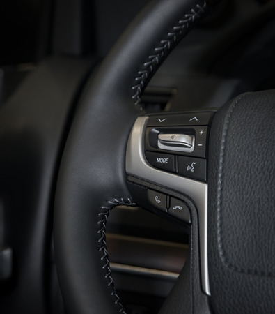 Hands free and media control buttons on the steering wheel, modern luxury car interior details