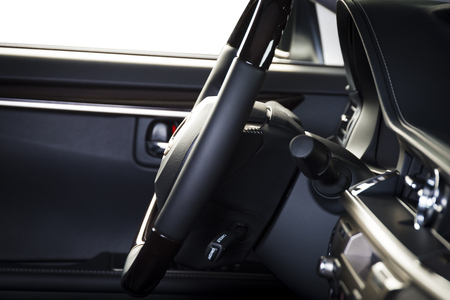 Modern luxury car  interior, dashboard, steering wheel, wood panels. Black perforated  leather interior, side view.