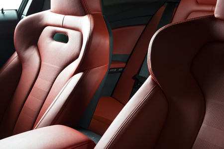 Luxury car inside. Interior of prestige modern car. Comfortable leather seats. Red perforated leather cockpit.