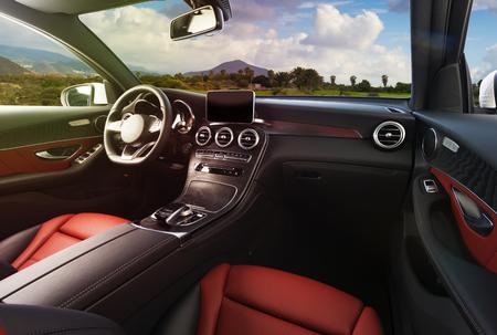 Nowoczesne luksusowe wnętrze samochodu - kierownica, dźwignia zmiany biegów i deska rozdzielcza. Luksusowe wnętrze samochodu. Kierownica, deska rozdzielcza, prędkościomierz, wyświetlacz. Kokpit z czerwono-czarnej skóry