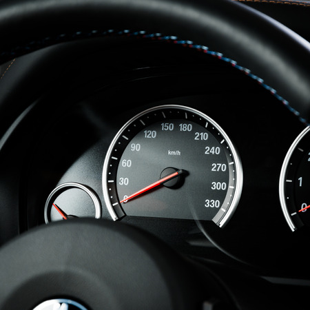 Close up shot of a speedometer in a car.