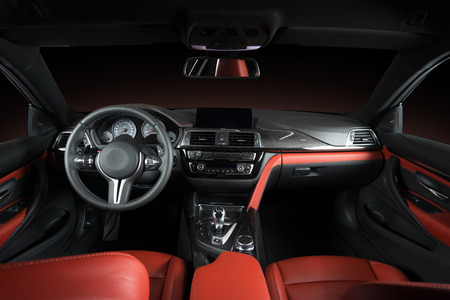 Modern luxury car Interior - steering wheel, shift lever and dashboard. Car interior luxury.Steering wheel, dashboard, speedometer, display. Red and black perforated leather cockpit Archivio Fotografico