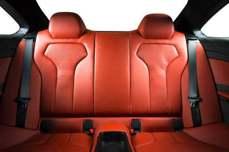 Back passenger seats in modern luxury car, frontal view, red perforated leather with stitching
