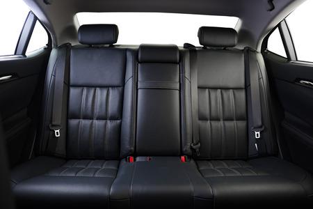 Hintere Passagiersitze im modernen Luxusauto, Vorderansicht, schwarzes perforiertes Leder, lokalisiert auf Weiß, Beschneidungspfad eingeschlossen.