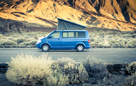 Small travel vehicle camping van or big car with folding rooftop with bed is parked under huge mountain formation. Tourism vacation and travel. Camper van and mountains landscape Reklamní fotografie