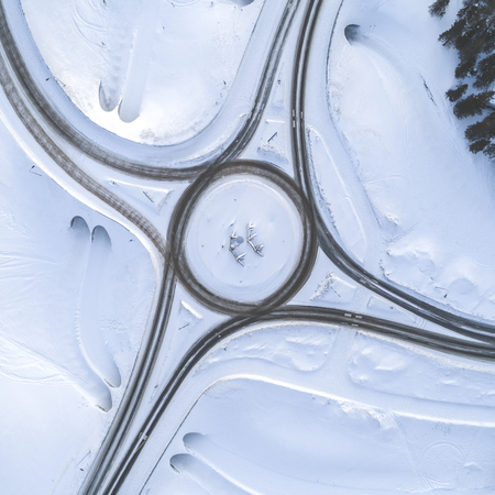 Aerial drone view of road in idyllic winter landscape. Street running through the nature from a birds eye view. Zdjęcie Seryjne