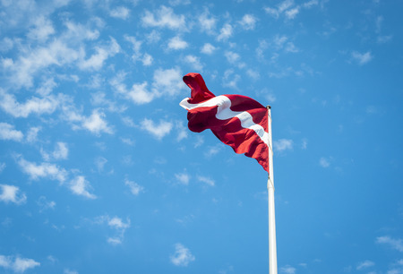 Latvia flag over blue sky with clouds background Stock fotó