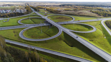 Aerial view of highway interchange  Road junction Aerial photo of a highway going through the forest Standard-Bild - 109611269