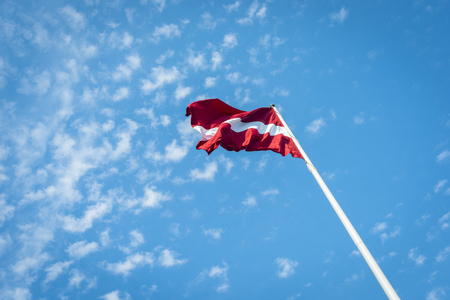 Latvia flag over blue sky with clouds background Standard-Bild - 109577810