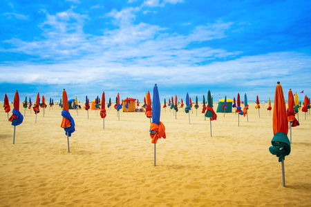 Lots of colorful closed umbrellas on the sunny summer beach with yellow sand