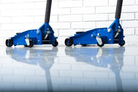 Two blue lift jacks in the car repair garage