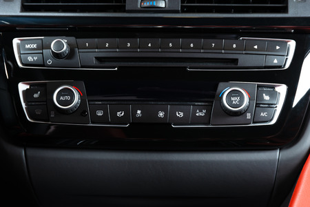 Media and air condition control buttons of a modern car. Car interior details. Black and red leather interior of the luxury modern car. A/C control panel Standard-Bild - 109577961