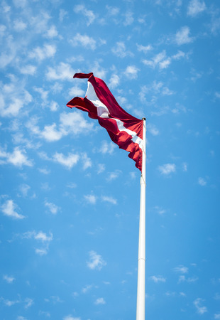 Latvia flag over blue sky with clouds background Stock Photo