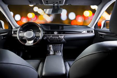 Interior del coche de lujo oscuro: volante, palanca de cambios y salpicadero. Coche adentro. Ciudad de noche borrosa Foto de archivo