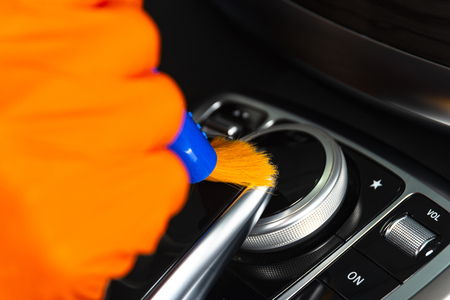 Brush cleaning off dust from the car interior details, control panel of the dashboard. A man cleaning car with cloth and brush. Car detailing.  Worker cleaning. Brush and cleaning solution to clean Imagens