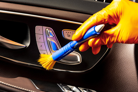 Brush cleaning off dust from the car interior details, control panel of the windows.  A man cleaning car with cloth and brush. Car detailing.  Worker cleaning. Brush and cleaning solution to clean the interior
